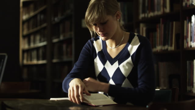 ms portrait of young woman reading book in library / buena vista, virginia, usa - blonde hair stock videos & royalty-free footage