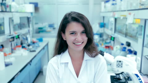 portrait of young woman scientists a smiling in laboratory, slow motion - biologist stock videos & royalty-free footage