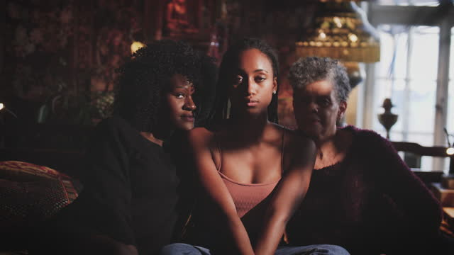 Portrait of young woman sitting amidst mother and grandmother at home