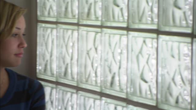 vídeos de stock, filmes e b-roll de cu pan portrait of young woman sitting by glass brick wall, brooklyn, new york city, usa - cabelo de comprimento médio