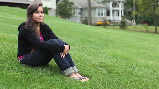 ws portrait of young woman sitting on grass in suburban area / cazenovia, new york, usa - flip flop stock videos and b-roll footage