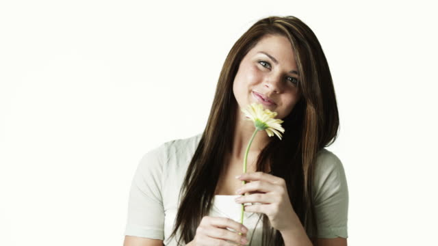 ms portrait of young woman smelling flower against white background / orem, utah, usa - orem utah stock videos & royalty-free footage