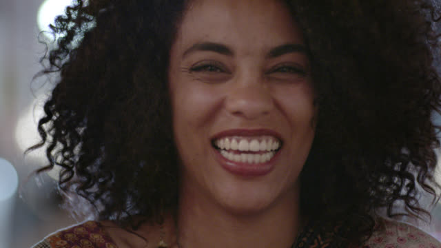 cu. portrait of young woman smiling and laughing at camera on city street at night. - sorridere video stock e b–roll