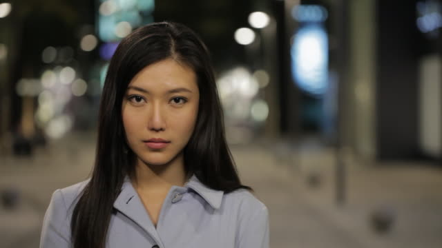 CU Portrait of young woman smiling at camera on city street at night / China