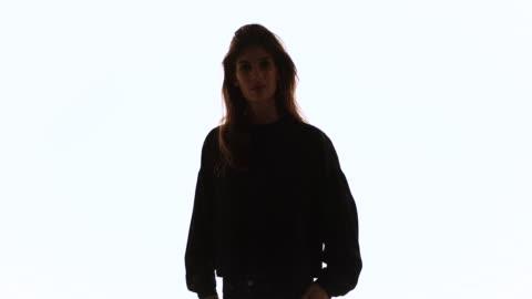 vidéos et rushes de portrait of young woman smiling at camera - cadrage à la taille