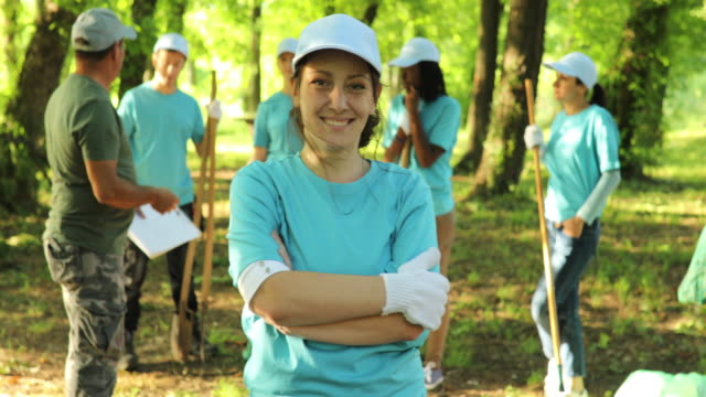 Portrait of young woman smiling while cleaning a public park