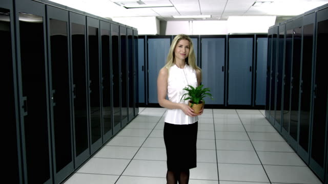 WS DS MS Portrait of young woman standing in server room, holding potted plant