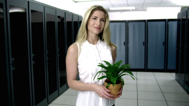 ms portrait of young woman standing in server room, holding potted plant - see other clips from this shoot 1480 stock videos and b-roll footage
