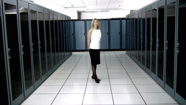 vídeos de stock e filmes b-roll de ws portrait of young woman standing in server room - full length