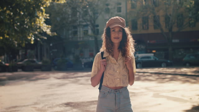portrait of young woman standing, smiling in sunshine in berlin - rucksack stock videos & royalty-free footage