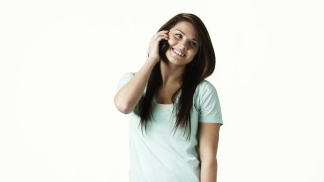 ms portrait of young woman talking on phone against white background / orem, utah, usa - orem utah stock videos & royalty-free footage