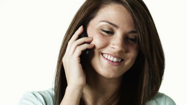 cu portrait of young woman talking on phone against white background / orem, utah, usa - orem utah stock videos & royalty-free footage