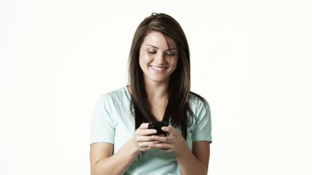 vídeos y material grabado en eventos de stock de ms portrait of young woman text-messaging against white background / orem, utah, usa - orem