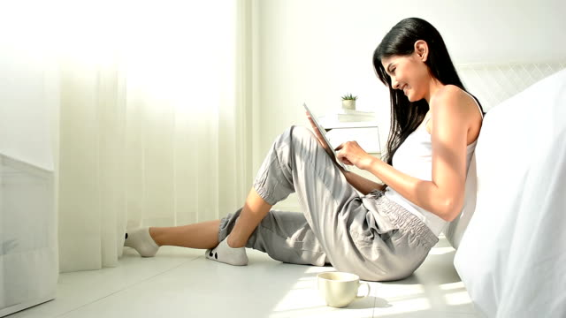 portrait of young woman using a digital tablet device at bedroom - beautiful woman stock videos & royalty-free footage