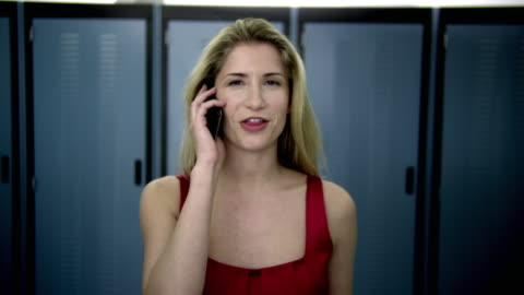 cu ds portrait of young woman walking in server room and talking on mobile phone - dolly shot stock videos & royalty-free footage