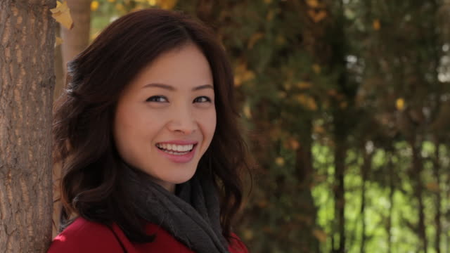 CU Portrait of young woman wearing scarf, standing in park / China