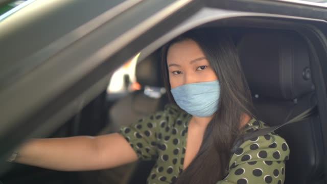 ritratto di giovane donna con maschera facciale all'interno della sua auto in un distributore di benzina - fare il pieno di benzina video stock e b–roll