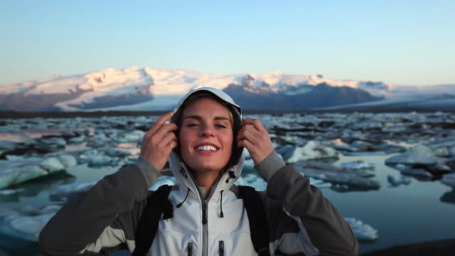 ms portrait of young woman with glacial lagoon in background, hofn, iceland - island stock-videos und b-roll-filmmaterial
