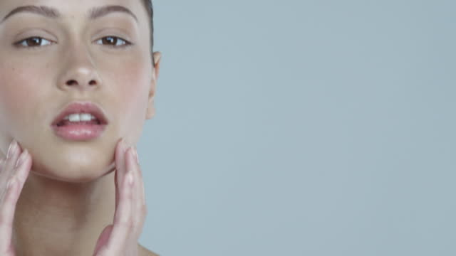 portrait of young woman with glowing skin touching face and looking to and away from camera and smiling - the human body stock videos and b-roll footage
