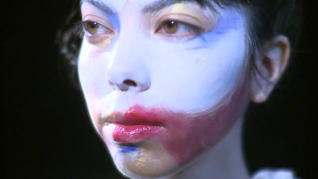 ecu portrait of young woman with painted face, new york city, new york, usa - chiaroscuro stock videos and b-roll footage