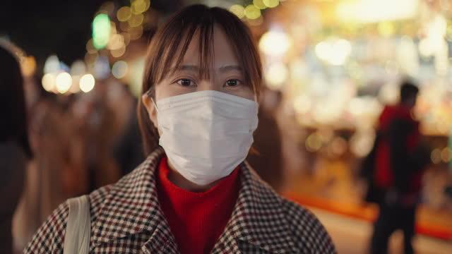 vidéos et rushes de verticale de jeune femme avec le masque protecteur de visage dans le marché de noël - profil