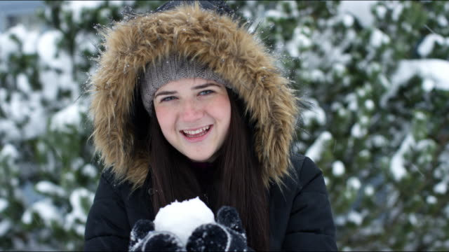 portrait of young woman with snowball, winter, vermont - wintermantel stock-videos und b-roll-filmmaterial