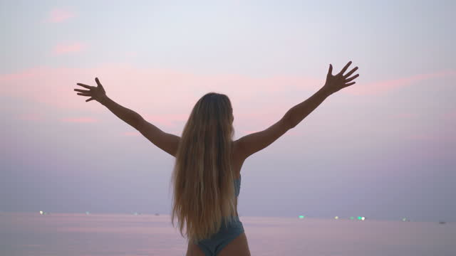 portrait of young women age 29 yearold of latin american and hispanic ethnicity posing raises arms into air while open arms enjoying the view and the wind on the beach.open arms concept. - wonderlust stock videos & royalty-free footage