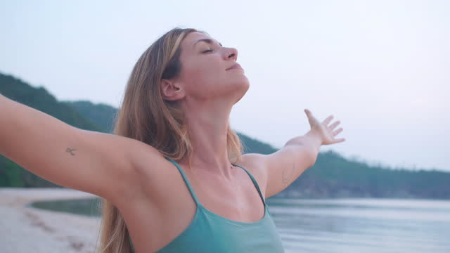 portrait of young women age 29 yearold of latin american and hispanic ethnicity posing raises arms into air while open arms with eyes closed enjoying the view and the wind on the beach. - wonderlust stock videos & royalty-free footage