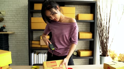 portrait of young women business owner standing and reading the barcode in home office doing small business. - e commerce stock videos & royalty-free footage