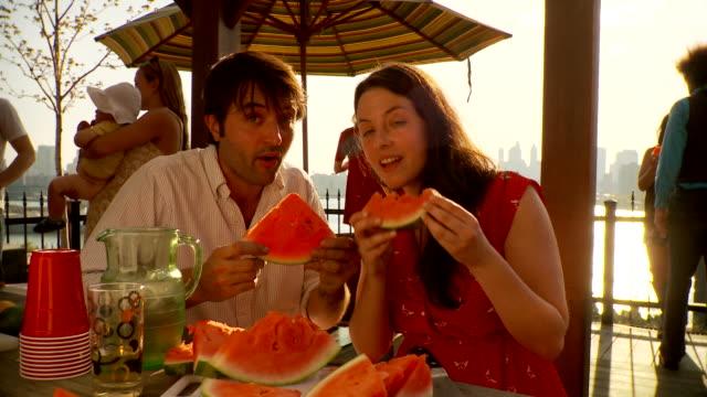 ms portrait op couple eating watermelon  / brooklyn, new york - mit handkamera stock-videos und b-roll-filmmaterial