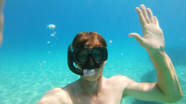 ms portrait playful man with wearable camera snorkeling underwater in sunny blue ocean,peljesac,croatia - swimming goggles stock videos & royalty-free footage