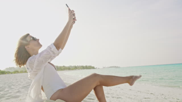 vídeos de stock e filmes b-roll de ms portrait playful woman taking selfie with digital tablet on sunny tropical ocean beach,maldives - descalço