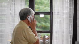 Portrait senior asian man talking on smartphone happy and smiling beside window at home. Slow motion