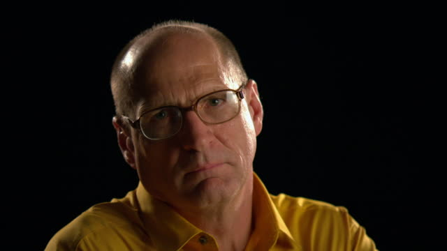 cu portrait senior, bald man with glasses on black background turns head to camera and glares - serious stock videos & royalty-free footage