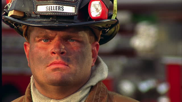 CLOSE UP portrait serious firefighter in helmet with dirty face