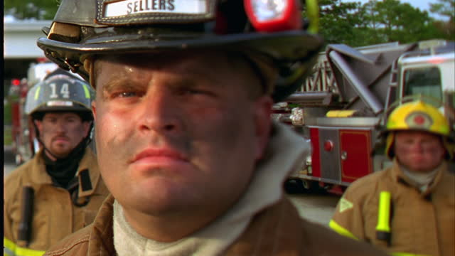 HANDHELD CLOSE UP portrait serious firefighter with dirty face turning to camera outdoors / others and fire truck in background\n