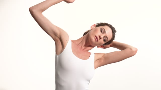 portrait shot of a classical ballet dancer dancing against a white backdrop - anmut stock-videos und b-roll-filmmaterial