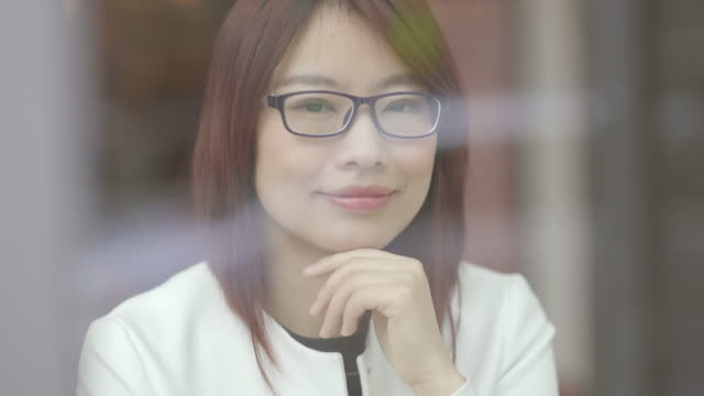 Portrait Shot of Attractive Asian Woman with Eyeglases Waiting in Lounge. Holding Hand to the Chin.