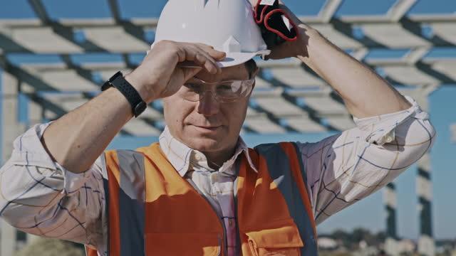 vidéos et rushes de slo mo portrait photo d'un entrepreneur en construction mettant un casque de travail sur sa tête sur le chantier de construction - bras croisés