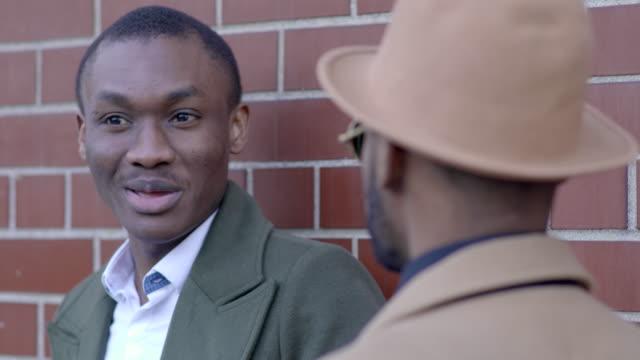 vidéos et rushes de portrait shot of two black african man having a conversation talking together about life - seulement des jeunes hommes