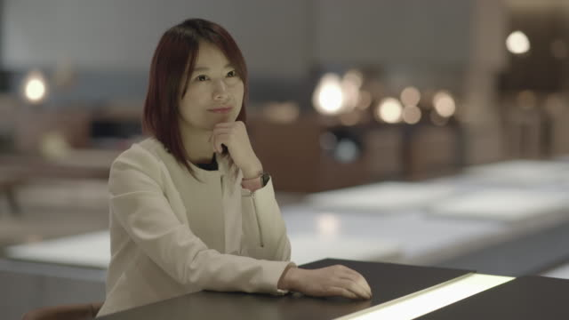 Portrait Shot of Young Asian Businesswoman Waiting in Lobby. Sitting at Table.