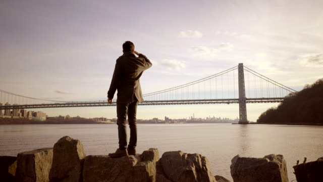 portrait shot of young asian man looking at water and bridge. cityscape in the background. - 手をかざす点の映像素材/bロール