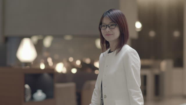 portrait shot of young asian woman wearing glasses and waiting in lobby. standing on floor. - mittellanges haar stock-videos und b-roll-filmmaterial