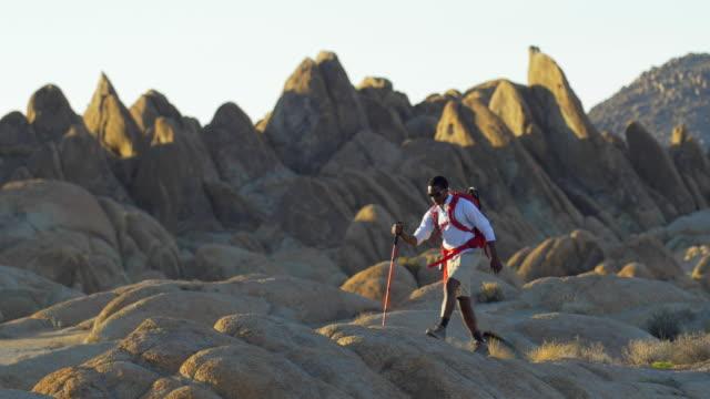 vidéos et rushes de portrait shot of young man backpacking over boulders in a mountainous desert. - seulement des jeunes hommes