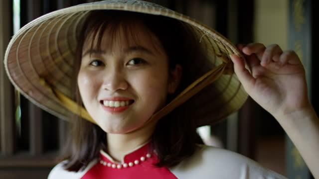 portrait smiling asian female wearing conical hat vietnam - 赤のドレス点の映像素材/bロール