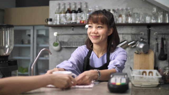 portrait smiling barista serving espresso at coffee shop counter - checkout stock videos and b-roll footage
