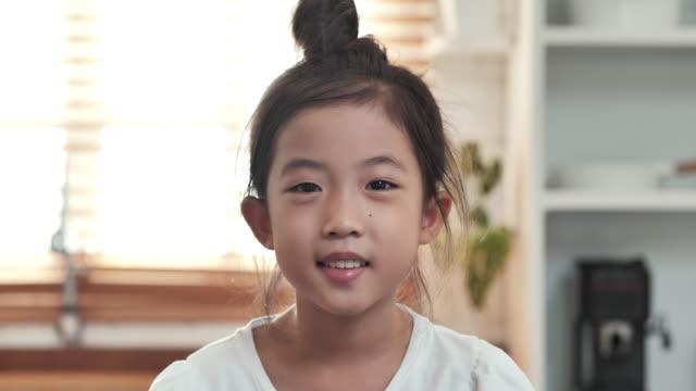 vídeos y material grabado en eventos de stock de retrato sonriendo confiado de niña asiática mirando cámara posando solo en casa con emoción feliz disfrutando de un estilo de vida exitoso. estudio casero - japonés oriental