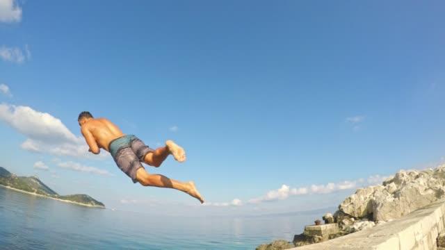 vídeos y material grabado en eventos de stock de 4k retrato sonriente hombre con cámara para filmar a amigo saltando en el océano de sol, verano, tiempo real - vestido parcialmente