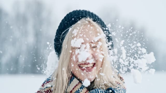 Portrait surprised woman getting hit with snowball, super slow motion