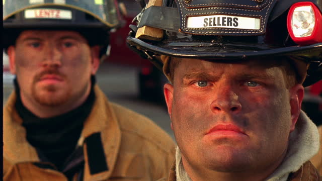 HANDHELD CLOSE UP TILT DOWN portrait two dirty firefighters in front of fire trucks.\n
